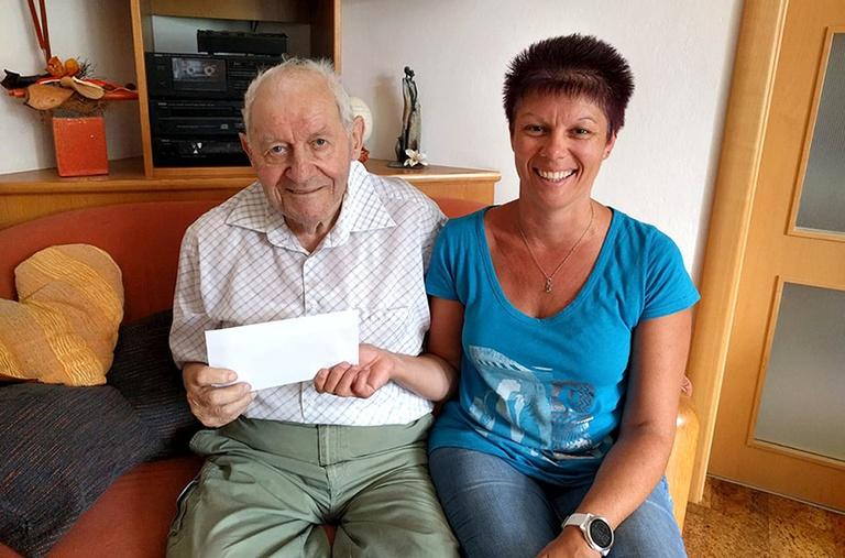Foto (S. Viertl): Josef Viertl übergibt Reisegutscheine an seine Enkelin Katrin Reithmayr, Hausleiterin in der Außenwohngruppe Traismauer-Stollhofen